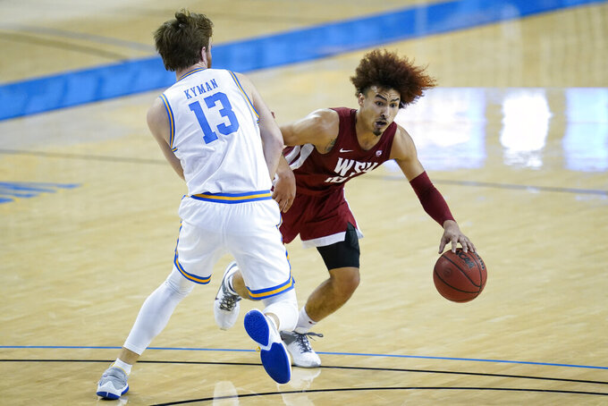 UCLA guard Jake Kyman (13) defends against Washington State guard Isaac Bonton, right, during the first half of an NCAA college basketball game Thursday, Jan. 14, 2021, in Los Angeles. (AP Photo/Ashley Landis)