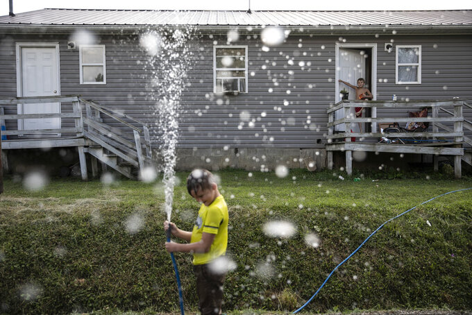 Gabriel Bonice, 7, left, and his brother, Donovyn, 8, play with a water hose on a hot summer's day at the back of their home in Bidwell, Ohio, on Monday, July 27, 2020. (AP Photo/Wong Maye-E)