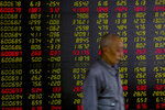 In this May 14, 2019, photo, a man walks past an electric board displaying stock prices at a brokerage house in Beijing. Asian markets were broadly lower on Thursday, May 23, 2019 as traders focused on tensions between the U.S. and China and braced for impact. (AP Photo/Andy Wong)
