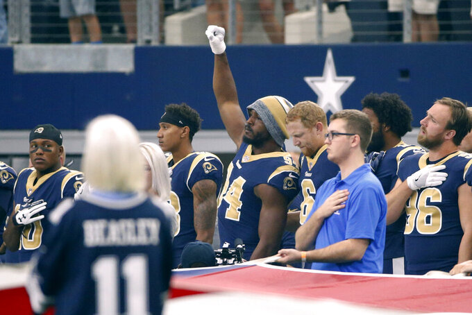 """FILE - In this Oct. 1, 2017, file photo, then-Los Angeles Rams linebacker Robert Quinn (94) raises his fist during the playing of the national anthem before an NFL football game against the Dallas Cowboys, in Arlington, Texas. Dallas Cowboys defensive end Robert Quinn says the issue of protesting during the national anthem """"might come up"""" before the season with owner Jerry Jones, who in the past has taken a hardline stance against displays by his players. Quinn joined the Cowboys in an offseason trade. (AP Photo/Ron Jenkins, File)"""