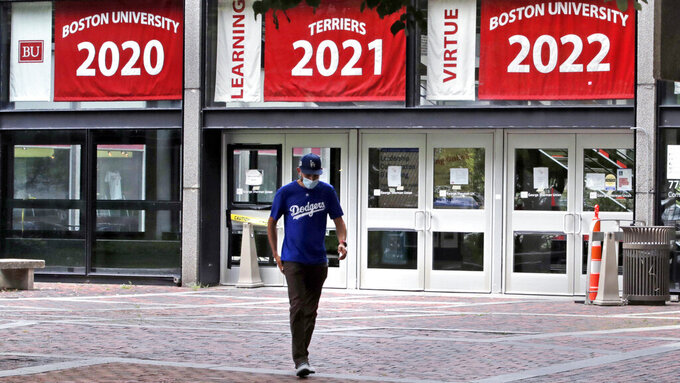 FILE - In this July 23, 2020, file photo, Weston Koenn, a graduate student from Los Angeles, leaves the Boston University student union building in Boston. The university is urging students to stay on campus for Thanksgiving or, if they go home, stay away for the rest of the semester, joining a growing number of U.S. universities working to curb the spread of the coronavirus around the holidays. (AP Photo/Charles Krupa, File)