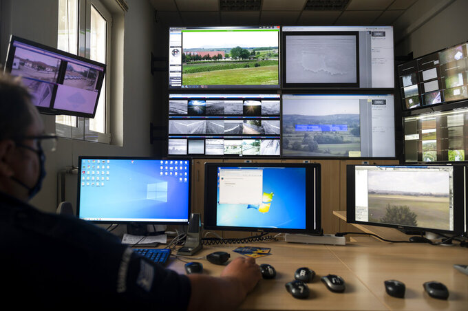 A police officer works inside the operation center at the village of Nea Vyssa near the Greek - Turkish border, Greece, Friday, May 21, 2021. An automated hi-tech surveillance network being built on the Greek-Turkish border aiming at detecting migrants early and deterring them from crossing, with river and land patrols using searchlights and long-range acoustic devices. (AP Photo/Giannis Papanikos)