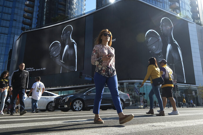 People walk past a mural of the late Kobe Bryan on a building near Staples Center, Monday, Jan. 27, 2020, in Los Angeles. Bryant, the 18-time NBA All-Star who won five championships and became one of the greatest basketball players of his generation during a 20-year career with the Los Angeles Lakers, died in a helicopter crash Sunday. (AP Photo/Ringo H.W. Chiu)