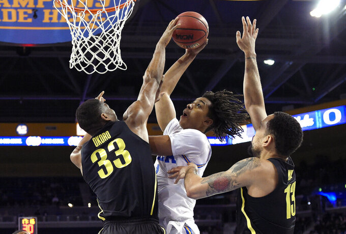 UCLA center Moses Brown, center, shoots as Oregon forward Francis Okoro, left, and forward Paul White defend during the first half of an NCAA college basketball game Saturday, Feb. 23, 2019, in Los Angeles. (AP Photo/Mark J. Terrill)