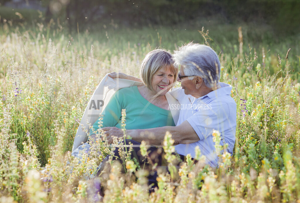 Man covering woman in blanket while sitting on meadow