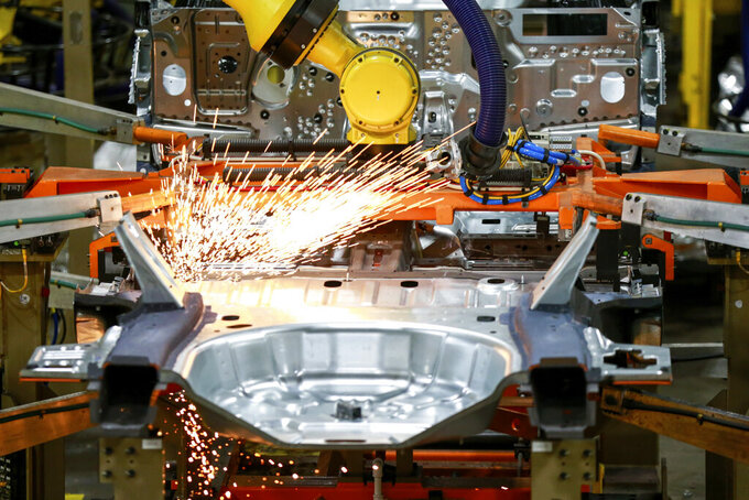 """FILE - In this June 24, 2019, file photo machines work on a Ford vehicle assembly line at Ford's Chicago Assembly Plant in Chicago.  Don't ditch those masks yet, autoworkers. A task force made up of union and car company officials said, Wednesday, May 19, 2021 it will continue to require workers to wear masks on the job """"out of an abundance of caution."""" The task force, represented by officials from United Auto Workers, Ford, General Motors and Stellantis said the mask requirement will remain in place until the Occupational Safety and Health Administration issues guidelines in response to the Centers for Disease Control and Prevention's recent change in COVID-19 workplace standards.    (AP Photo/Amr Alfiky, File)"""
