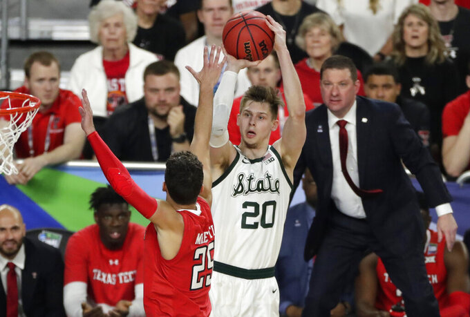 Michigan State guard Matt McQuaid (20) shoots over Texas Tech guard Davide Moretti during the first half in the semifinals of the Final Four NCAA college basketball tournament, Saturday, April 6, 2019, in Minneapolis. (AP Photo/Matt York)