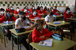 A group of young students wearing face mask protection to prevent the spread of the coronavirus attend their first class in Luis Amigo school, in Pamplona, northern Spain, Monday, Sept. 7, 2020. Students in five Spanish regions return to class on Monday for the first time since the pandemic paralyzed Spain six months ago. (AP Photo/Alvaro Barrientos)