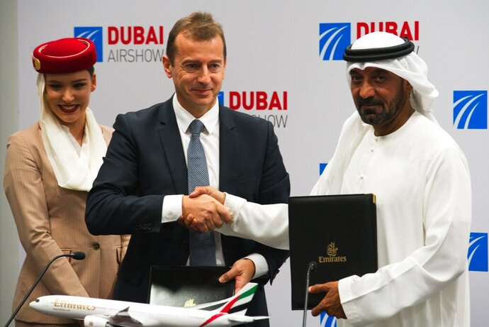 Airbus CEO Guillaume Faury, center, shakes hands with Sheikh Ahmed bin Saeed Al Maktoum, the chairman and CEO of the Dubai-based long-haul carrier Emirates, at the Dubai Airshow in Dubai, United Arab Emirates, Monday, Nov. 18, 2019. The Dubai-based airline Emirates announced Monday a new order for 20 additional wide-body Airbus A350-900 planes in a deal worth $6.4 billion. This brings the airline's total order for the aircraft to 50 Airbus A350s costing $16 billion at list price. (AP Photo/Jon Gambrell)