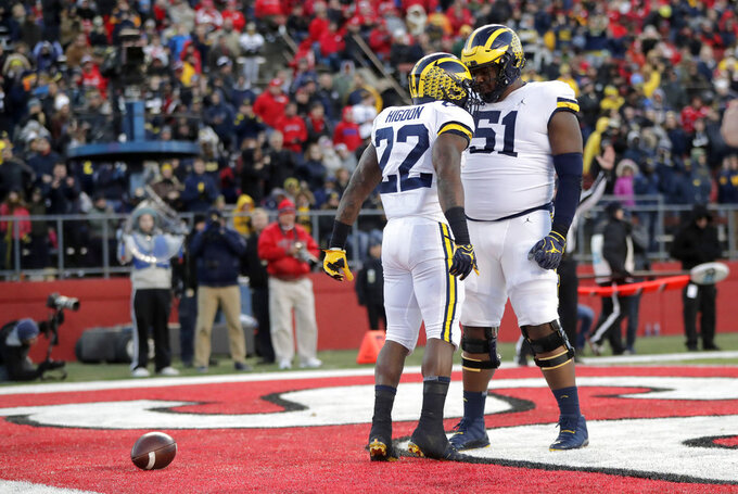 Michigan running back Karan Higdon (22) celebrates his touchdown run with offensive lineman Cesar Ruiz (51) during the first half of an NCAA college football game against Rutgers, Saturday, Nov. 10, 2018, in Piscataway, N.J. (AP Photo/Julio Cortez)