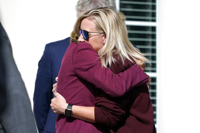 Hollie Skaggs, right, is hugged after a prayer vigil at the Collierville Town Hall Friday, Sept. 24, 2021, in Collierville, Tenn. Skaggs was shopping in a Kroger grocery store Thursday when a gunman attacked people, killing one and injuring others, before he was found dead of an apparent self-inflicted gunshot wound. (AP Photo/Mark Humphrey)