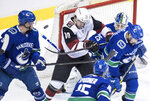 The puck goes wide of the net as Arizona Coyotes' Jordan Weal (10) checks Vancouver Canucks' Alex Biega (55) in front of goalie Jacob Markstrom, back right, of Sweden, as Derrick Pouliot, left, and Ryan Spooner watch during the second period of an NHL hockey game Thursday, Feb. 21, 2019, in Vancouver, British Columbia. (Darryl Dyck/The Canadian Press via AP)