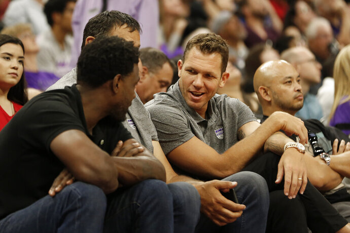 "FILE - In this July 1, 2019, file photo, Sacramento Kings head coach Luke Walton talks with former Sacramento Kings player Chris Webber, left, as Kings general manager Vlade Divac, obscured at center, looks on during the first half of an NBA basketball summer league gamebetween the Kings and Golden State Warriors in Sacramento, Calif. The Sacramento Kings and the NBA have announced that after a thorough investigation there isn't enough evidence to support allegations that new coach Luke Walton sexually assaulted a woman. The team and league began a joint investigation in April following a lawsuit filed in Los Angeles by former sportscaster Kelli Tennant, who ""elected not to participate in the investigation. Based on this and the available evidence, the investigators determined that there was not a sufficient basis to support the allegations made against Coach Walton,"" the Kings announced in a joint statement with the NBA. (AP Photo/Rich Pedroncelli, File)"