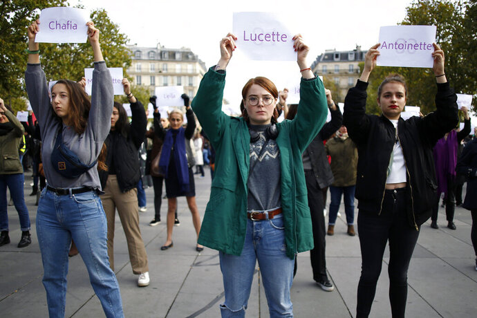 FILE - In this Oct.19, 2019 file photo, women hold placards with the names of women killed by their partners, during a protest, in Paris. France, a country that has prided itself on gender equality, is beginning to pay serious attention to its yet-intractable problem of domestic violence. (AP Photo/Thibault Camus, File)
