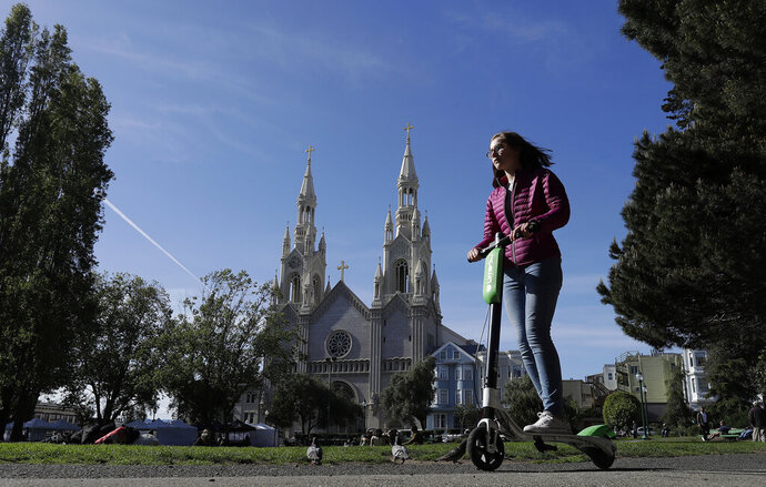 FILE - In this April 17, 2018 file photo, a woman rides a motorized scooter in Washington Square Park in San Francisco. Tired of San Francisco sidewalks being used as a testing ground for delivery robots, drones, and electric scooters, city supervisors will vote Tuesday, Dec. 10, 2019, to set up a new regulatory office that would require businesses to get permits before trying out new technology that uses public space.  (AP Photo/Jeff Chiu, File)