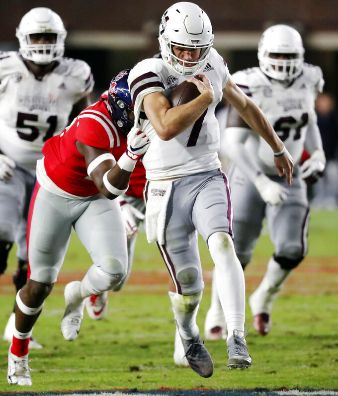 Mississippi State quarterback Nick Fitzgerald (7) is pulled down by a Mississippi defender after a first-down run during the first half of an NCAA college football game in Oxford, Miss., Thursday, Nov. 22, 2018. (AP Photo/Rogelio V. Solis)