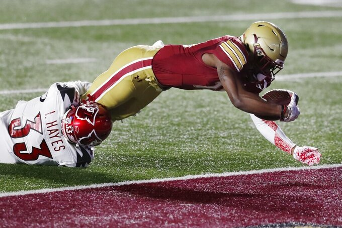 Boston College wide receiver Jehlani Galloway scores against Louisville defensive back Isaiah Hayes (33) during the second half of an NCAA college football game Saturday, Nov. 28, 2020, in Boston. (AP Photo/Michael Dwyer)