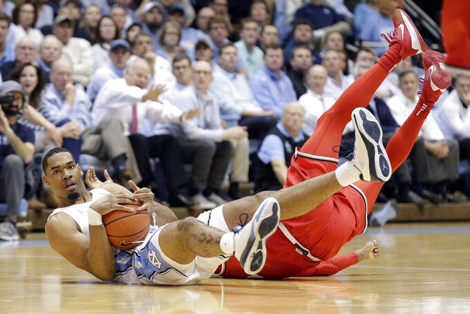 North Carolina forward Garrison Brooks holds the ball while Ohio State guard Luther Muhammad falls to the floor during the first half of an NCAA college basketball game in Chapel Hill, N.C., Wednesday, Dec. 4, 2019. (AP Photo/Gerry Broome)