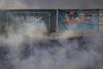 Banners advertising new homes are seen behind smoke from a grass fire as the Silverado Fire threatens residential areas Monday, Oct. 26, 2020, in Irvine, Calif. (AP Photo/Jae C. Hong)