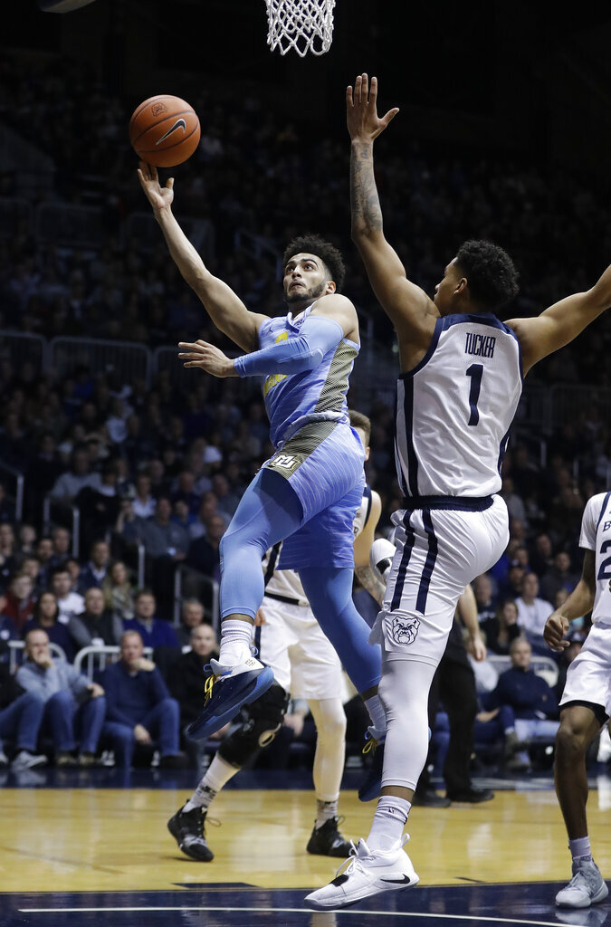Marquette's Markus Howard (0) puts up a shot against Butler's Jordan Tucker (1) during the second half of an NCAA college basketball game, Wednesday, Jan. 30, 2019, in Indianapolis. Marquette won 76-58. (AP Photo/Darron Cummings)