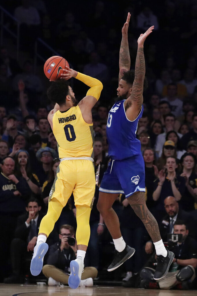 Marquette guard Markus Howard (0) shoots against Seton Hall guard Myles Powell during the second half of an NCAA college basketball semifinal game in the Big East men's tournament, Friday, March 15, 2019, in New York. Seton Hall won 81-79. (AP Photo/Julio Cortez)