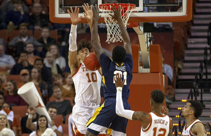 Texas forward Jaxson Hayes (10) blocks a dunk attempt by West Virginia forward Wesley Harris (21) during an NCAA college basketball game on Saturday, Jan. 5, 2019, in Austin, Texas. (Nick Wagner/Austin American-Statesman via AP)