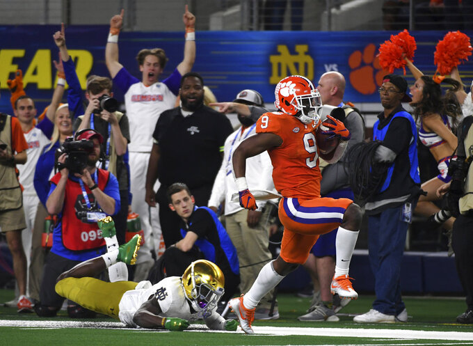 Notre Dame safety Jalen Elliott, left, is unable to stop Clemson running back Travis Etienne (9) from reaching the end zone for a touchdown in the second half of the NCAA Cotton Bowl semi-final playoff football game, Saturday, Dec. 29, 2018, in Arlington, Texas. (AP Photo/Jeffrey McWhorter)