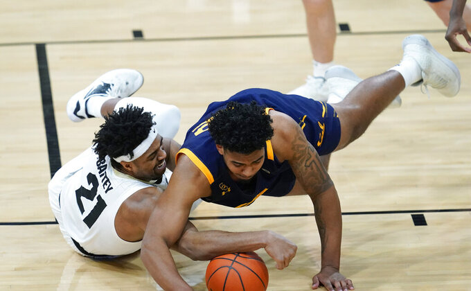 Colorado forward Evan Battey, left, battles for control of a loose ball with California forward Andre Kelly in the second half of an NCAA college basketball game Thursday, Jan. 14, 2021, in Boulder, Colo. Colorado won 89-60. (AP Photo/David Zalubowski)