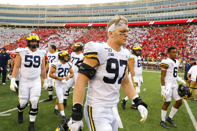 Michigan defensive lineman Aidan Hutchinson walks off the field with his teammates after losing 35-14 to Wisconsin in an NCAA college football game Saturday, Sept. 21, 2019, in Madison, Wis. (AP Photo/Andy Manis)