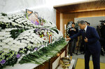South Korean President Moon Jae-in places a flower at a memorial altar for the late former sex slave and activist Kim Bok-dong, Wednesday, Jan. 29, 2019, in Seoul, South Korea. Hundreds of South Koreans are mourning Kim's death in Seoul Wednesday demanding reparations from Tokyo over their wartime atrocities. (Bee Jae-man/Yonhap via AP)
