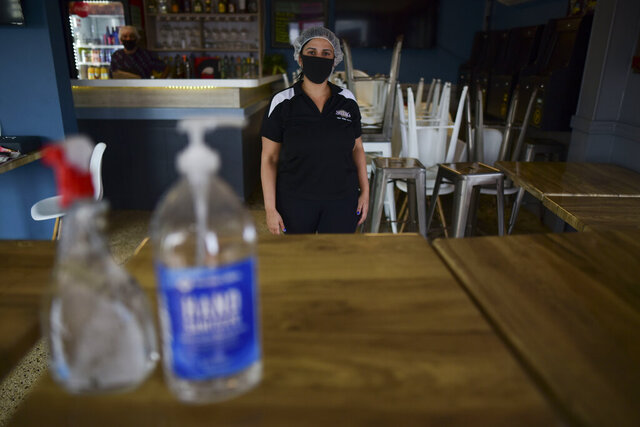 Elismarie Cruz, manager at Sarkis restaurant, wears a mask as a precaution against COVID-19 while standing in the middle of an improvised food delivery station, in Canovanas, Puerto Rico, Thursday, May 21, 2020. Puerto Rico is cautiously reopening beaches, restaurants, churches, malls, and hair salons under strict conditions as the U.S. territory emerges from a two-month lockdown despite dozens of new coronavirus cases reported daily. (AP Photo/Carlos Giusti) PUERTO RICO OUT-NO PUBLICAR EN PUERTO RICO