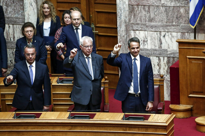Greek Prime Minister Kyriakos Mitsotakis, right, Deputy Prime Minister Panagiotis Pikrammenos, center, and Finance Minister Christos Staikouras, left, take the oath during a swearing in ceremony at the parliament in Athens, Wednesday, July 17, 2019. Greece held its first parliamentary session after the general elections held on July 7. (AP Photo/Yorgos Karahalis)