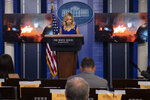 White House press secretary Kayleigh McEnany stands as a video from Portland, Ore., is shown during a press briefing in the James Brady Press Briefing Room at the White House, Friday, July 24, 2020, in Washington. (AP Photo/Alex Brandon)