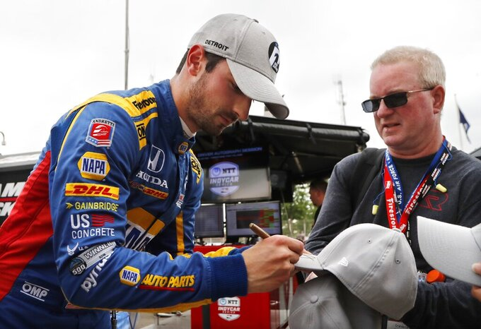 Alexander Rossi autographs caps after qualifying for the pole for the first race of the IndyCar Detroit Grand Prix auto racing doubleheader, Saturday, June 1, 2019, in Detroit. (AP Photo/Carlos Osorio)