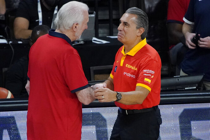 United States head coach Gregg Popovich, left, shakes hands with Spain head coach Sergio Scariolo after an exhibition basketball game in preparation for the Olympics, Sunday, July 18, 2021, in Las Vegas. (AP Photo/John Locher)