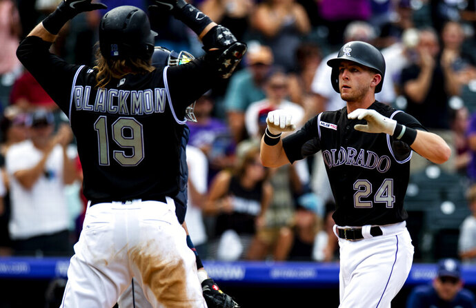 Colorado Rockies' Ryan McMahon (24) celebrates with Charlie Blackmon (19) after hitting a home run against the San Diego Padres in the third inning of a baseball game Sunday, Sept. 15, 2019, in Denver. (AP Photo/Parker Seibold)