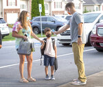 Holston View Elementary School Program Assistant Trey Arrington takes the temperature of 1st grader Cash Duty as he walks into the school with his mother, Nicolette, on Monday, Aug. 24, 2020, in Bristol, Tennessee. (David Crigger/Bristol Herald Courier via AP)