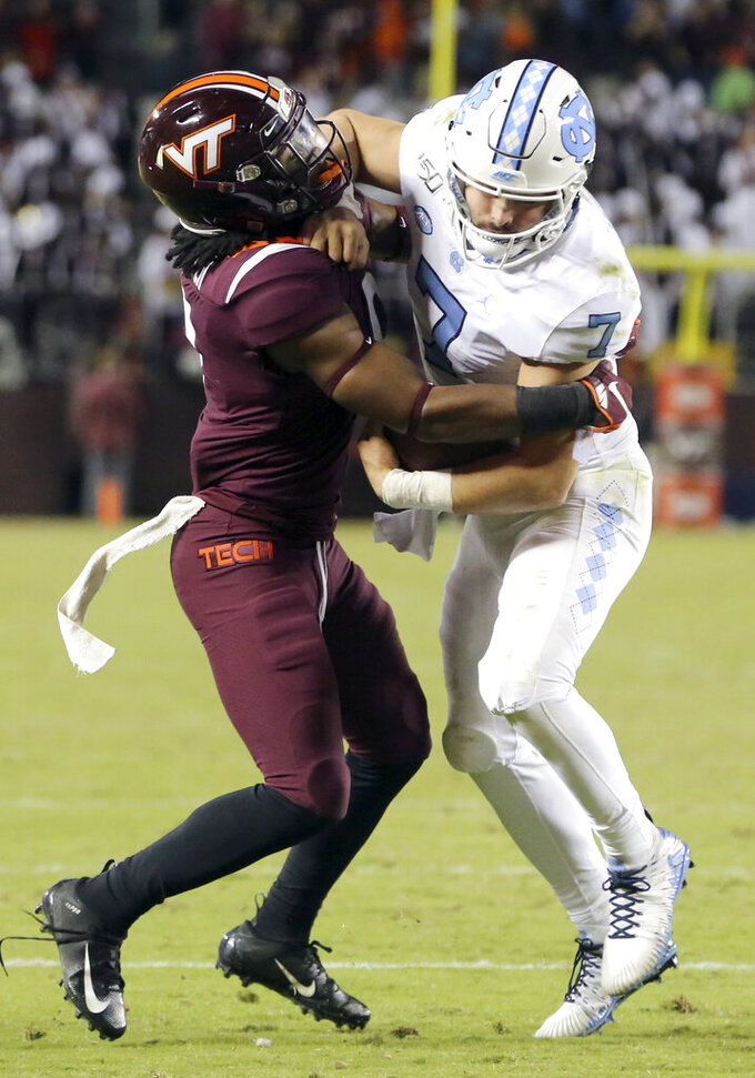 North Carolina quarterback Sam Howell (7) is tackled by Virginia Tech defender Khalil Ladler, left, in the final overtime of an NCAA college football game Saturday, Oct. 19, 2019, in Blacksburg, Va. (Matt Gentry/The Roanoke Times via AP)