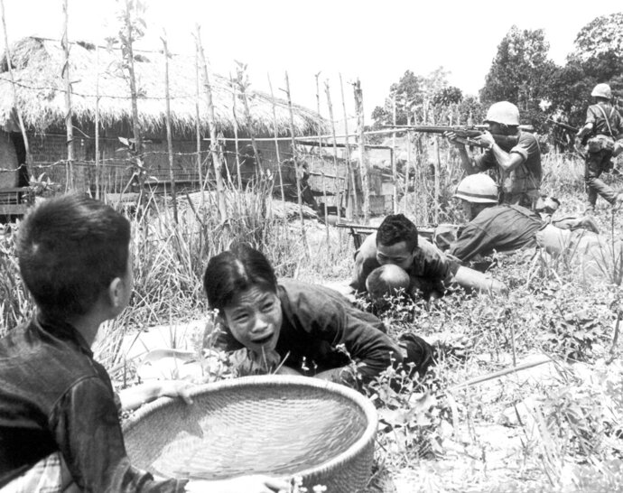 FILE - In this April 1965 under sniper fire, Vietnamese civilians duck for safety as U.S. Marines storm the village of My Son, near Da Nang in Vietnam searching for Viet Cong insurgents. The Vietnamese capital once trembled as waves of American bombers unleashed their payloads, but when Kim Jong Un arrives here for his summit with President Donald Trump he won't find rancor toward a former enemy. Instead, the North Korean leader will get a glimpse at the potential rewards of reconciliation. (AP Photo/Eddie Adams, File)