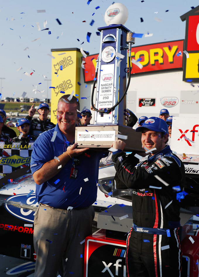 Matt Sampson, left, and Chase Briscoe, right, hold up a NASCAR Xfinity Series auto race championship trophy, Saturday, July 27, 2019, at Iowa Speedway in Newton, Iowa. (AP Photo/Matthew Putney)