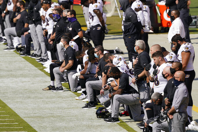 The Baltimore Ravens, some kneeling, participate in the national anthem before the first half of an NFL football game between the Washington Football Team and the Baltimore Ravens, Sunday, Oct. 4, 2020, in Landover, Md. (AP Photo/Susan Walsh)