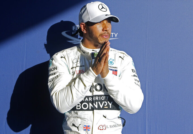 Mercedes driver Lewis Hamilton of Britain puts his hands together after qualifying on pole for the Australian Grand Prix in Melbourne, Australia, Saturday, March 16, 2019. The first race of the year is Sunday. (AP Photo/Rick Rycroft)