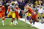 Clemson linebacker Isaiah Simmons pulls off a piece of tape on LSU wide receiver Ja'Marr Chase during the second half of a NCAA College Football Playoff national championship game Monday, Jan. 13, 2020, in New Orleans. (AP Photo/Sue Ogrocki)