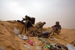 FILE - In this Saturday, Feb. 21, 2015 file photo, Libyan soldiers aim their weapons during clashes with militants on the frontline in Al Ajaylat, 120 kilometers (75 miles) west of Tripoli, Libya. The United Nations said Friday, Oct. 23, 2020, that the two sides in Libyan military talks had reached a