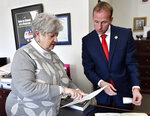 Mary Sue Helm, Executive Director of the Kentucky Office of Elections, left, goes over the filing documents with state Rep. Robert Goforth, R-East Bernstadt, as he files to be a candidate for Governor at the Kentucky State Capitol in Frankfort, Ky., Tuesday, Jan. 8, 2019. (AP Photo/Timothy D. Easley)
