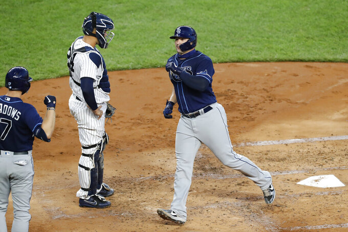 Tampa Bay Rays catcher Mike Zunino, right, crosses the plate after hitting a solo home run and before greeting the Rays Austin Meadows, left, during the third inning of a baseball game against the New York Yankees, Wednesday, Aug. 19, 2020, in New York. Yankees catcher Gary Sanchez (24) stands with his hands on his hips. (AP Photo/Kathy Willens)