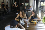 Patrons eat lunch at Slater's 50/50 Wednesday, July 1, 2020, in Santa Clarita, Calif. California Gov. Gavin Newsom has ordered a three-week closure of bars, indoor dining and indoor operations of several other types of businesses in various counties, including Los Angeles, as the state deals with increasing coronavirus cases and hospitalizations. (AP Photo/Marcio Jose Sanchez)