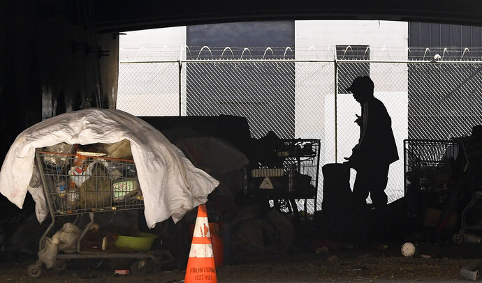 FILE - In this May 21, 2020 file photo, a man is seen at a homeless encampment that sits under Interstate 110 near Ramirez Street during the coronavirus outbreak in downtown Los Angeles. The number of homeless people counted across Los Angeles County jumped 12.7% over the past year to more than 66,400, according to data released Friday, June 12, by the Los Angeles Homeless Services Authority. Authorities fear that figure will spike again once the full impact of the coronavirus pandemic is felt. (AP Photo/Mark J. Terrill, File)