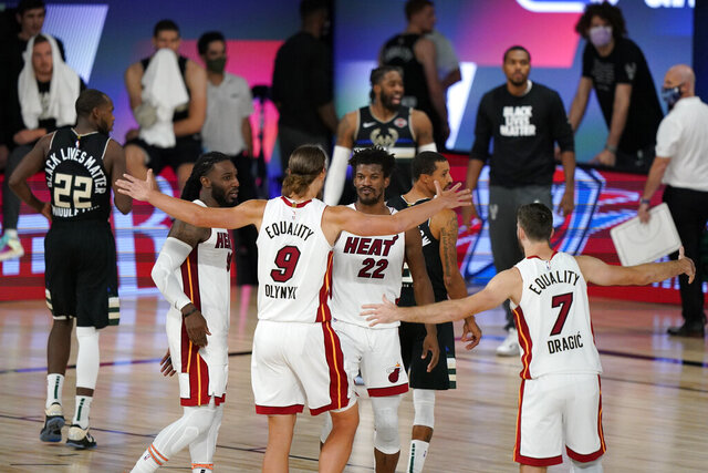 Miami Heat's Kelly Olynyk (9) and Jimmy Butler (22) react with teammates after the Heat beat the Milwaukee Bucks 116-114 in an NBA conference semifinal playoff basketball game Wednesday, Sept. 2, 2020, in Lake Buena Vista, Fla. (AP Photo/Mark J. Terrill)