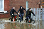 Teenagers ride their bikes through floodwater in Doncaster, northern England, Friday, Nov. 8, 2019. Torrential rain has drenched parts of north and central England, forcing some to evacuate their homes and stranding a small group of people in a shopping center overnight. Floods hit the city of Sheffield, where the River Don overflowed after 3.4 inches (85 mm) of rain fell on Thursday. The Environment Agency says the highest rainfall was registered in Swineshaw, in the Peak District — 4.4 inches (112 mm) in the same period. (Danny Lawson/PA via AP)